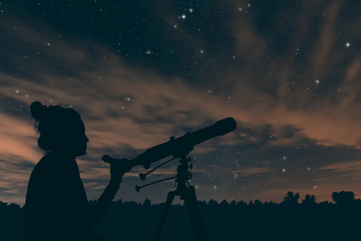 Woman with telescope. Night sky, with clouds and constellations,